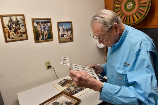 Mike Labriola, who was instrumental in getting the Lewis and Clark Interpretive Center built in the 1990's, looks through slides from the early days of the Lewis and Clark Honor Guard.