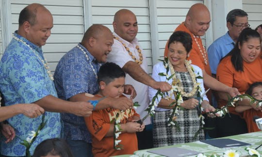 "From left, education Superintendent Jon Fernandez, school board Chairman Mark Mendiola, 7-year-old Dean Teria, Lt. Gov. Joshua Tenorio and Gov. Lou Leon Guerrero on April 22 prepare to cut a ceremonial ""ribbon"" at P.C. Lujan Elementary School, to celebrate the start of a new CHamoru language immersion program. Teria attended a summer school program by the Chief Hurao Academy, which will be sharing the school facility with the new immersion program."