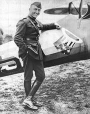 "World War I flying ace Eddie Rickenbacker is shown standing beside one of the planes he piloted.  It bears the famous ""hat in ring"" insignia of his 94th Aero Squadron which he commanded.  The insignia was also present on his production vehicles."