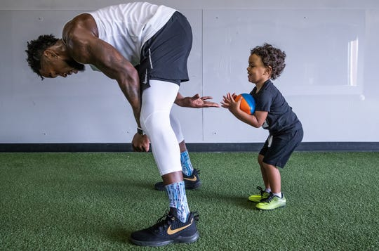 """""""Hike!"""" yells Justin Brent, as he hands a Nerf football to his son, Braxton, 2, at Sparx Athletic Refinery in Fishers, Ind., on Monday, April 22, 2019. """"Alright, throw it!"""" Brent includes his son in his training to show him what hard work can bring."""