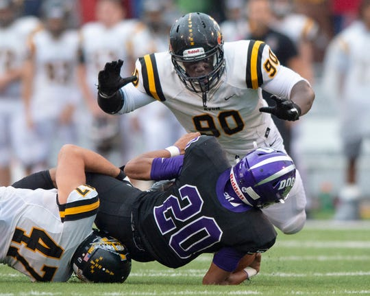 Avon's Nathaniel James (90) closes in on Brownsburg's Donny Marcus (20).