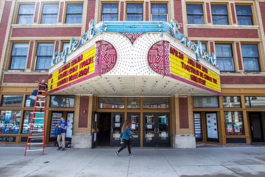 Englert box office staffer Matt Heidel, top left, changes letters on the marquee with help from house manager Dan Stolley, Monday, April 22, 2019, outside the Englert Theater along Washington Street in Iowa City, Iowa.