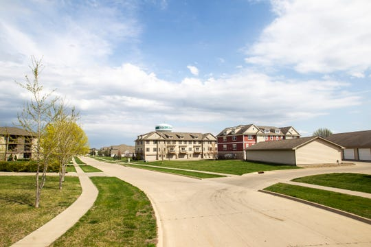 Trees wave in the wind in a neighborhood with multiplex apartment housing and condos, Monday, April 22, 2019, along Penn Court near Centennial Park in North Liberty, Iowa.