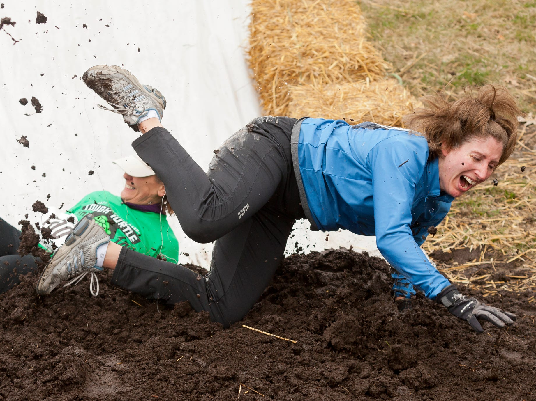 2014: Jennifer Gray of Ithaca hits the compost at the bottom of the plastic slide Saturday morning during the annual Tough Turtle event held to benefit the Children's Garden.