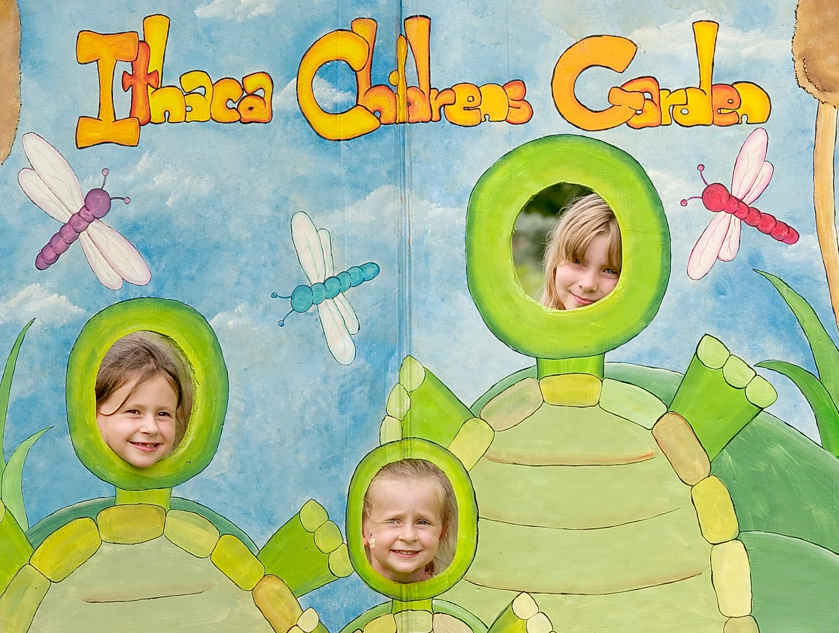 2006:  Elsa Konieczynski, 6, her sister Lauren, 3, and Joella Sloand, 9, pose for photos by a mural at the Ithaca Children's Garden during the garden's Second Annual Turtle Hatchday Celebration Saturday in Cass Park. Festivities included face painting, storytelling, cake and ice cream.