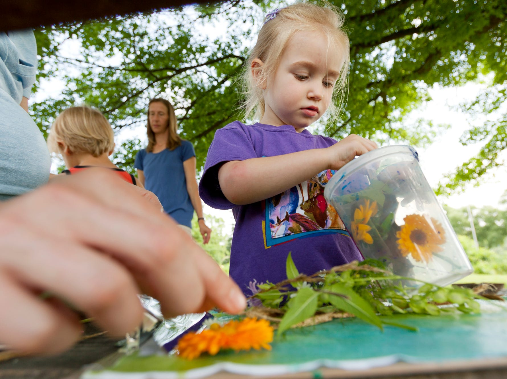 2013: Three-year-old Lilie Stevens of Trumansburg, gets some help Tuesday morning from her mother, Kathryn Reeves as they make a colored photogram at the Children's Garden.