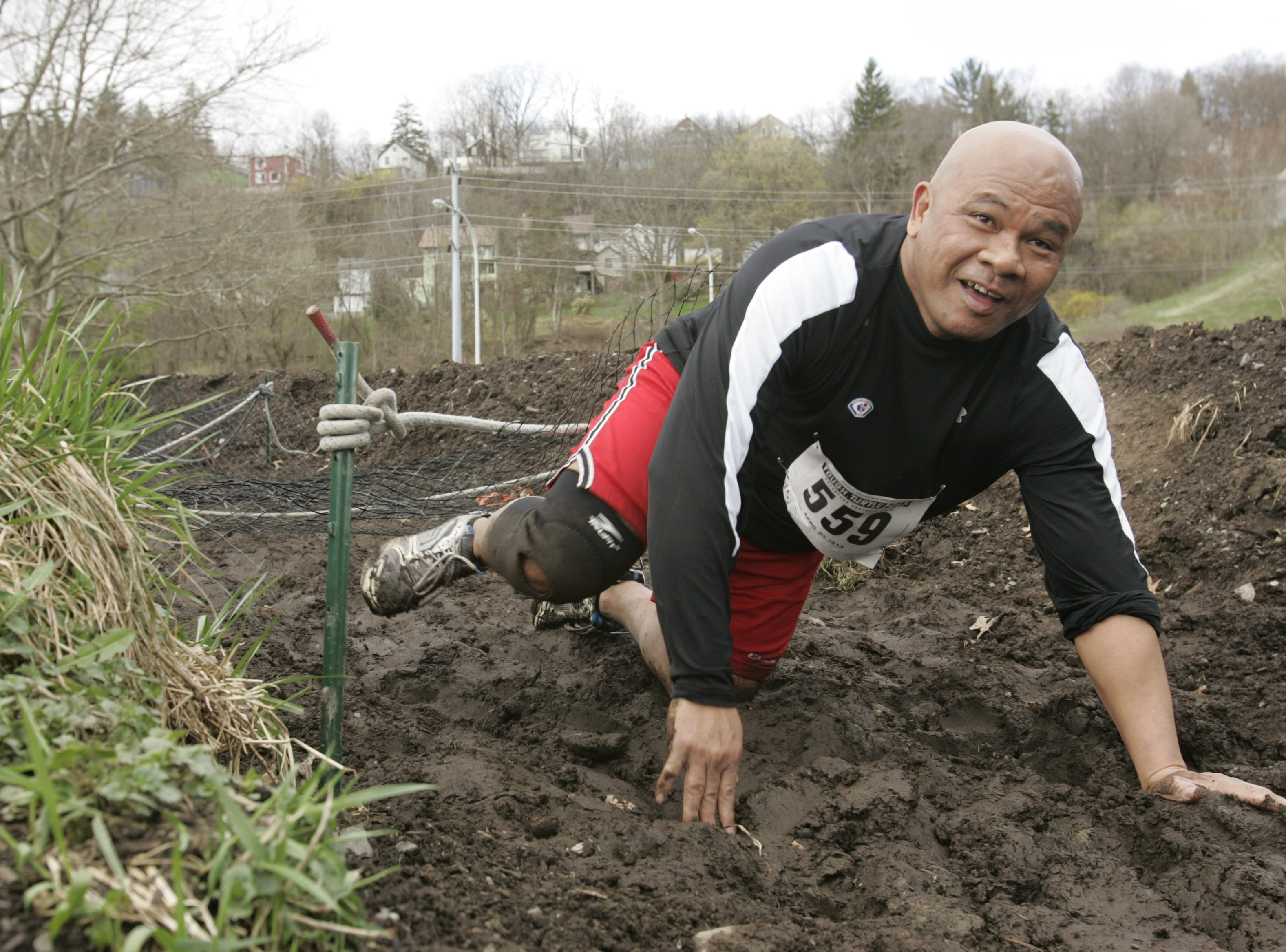 2013: A racer scrambles through the mud near the finish line at the Tough Turtle race held Saturday in Ithaca. The race benefits the Ithaca Children's Garden.