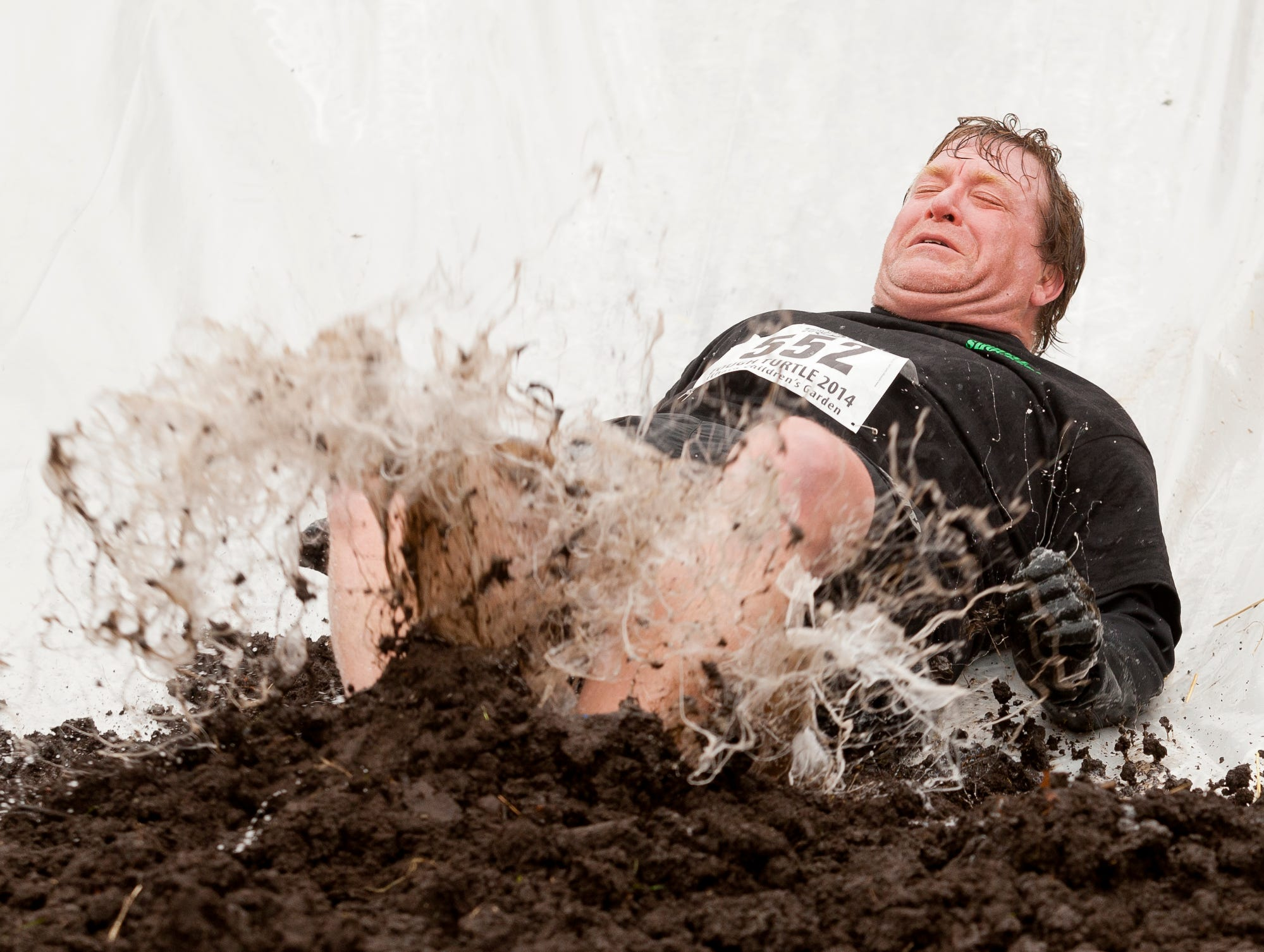 2014: Marvin Oltz of Ithaca hits the compost at the bottom of the plastic slide during the annual Tough Turtle event held in April to benefit the Children's Garden.