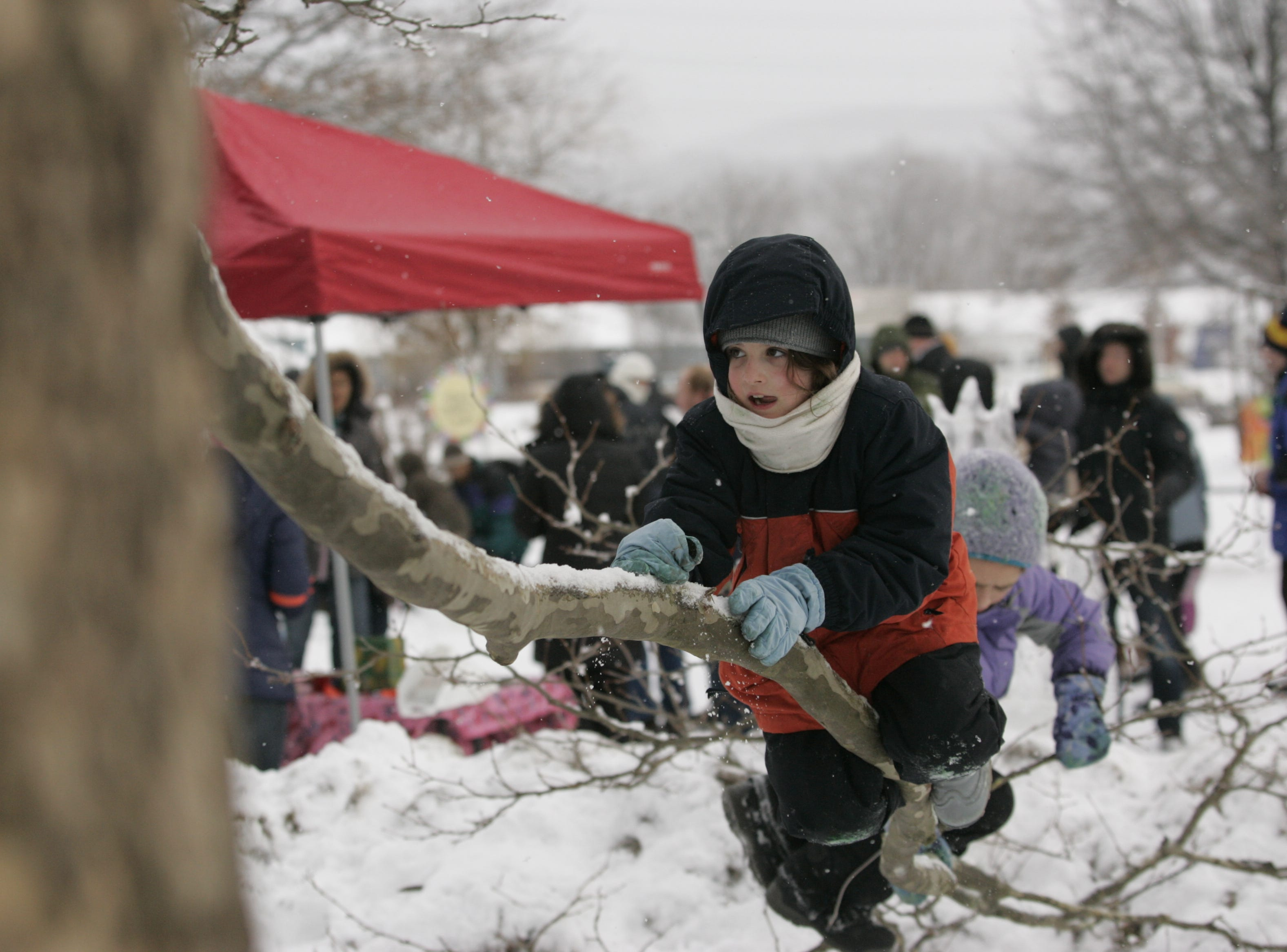 2013: Cady Austin, 9, of Spencer, climbs a tree branch with her friend Lydia Diboun, 9, Van Etten, during the Fire and Ice Festival on Saturday.