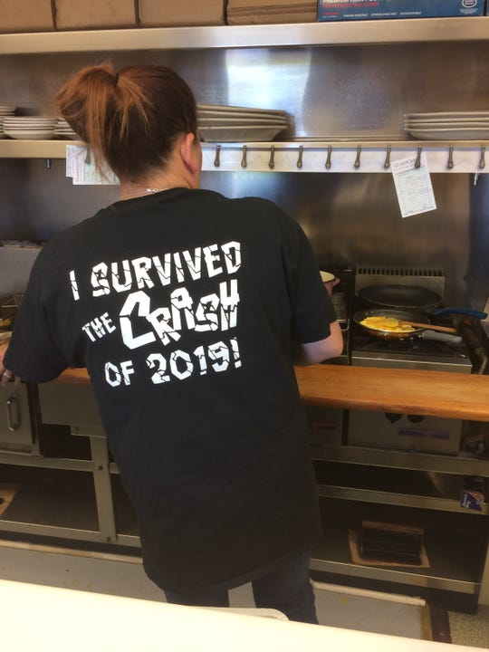 Chrissy Tillman wears one of the shirts she bought for the staff to celebrate the reopening after a car came through the front of Scottie's restaurant.