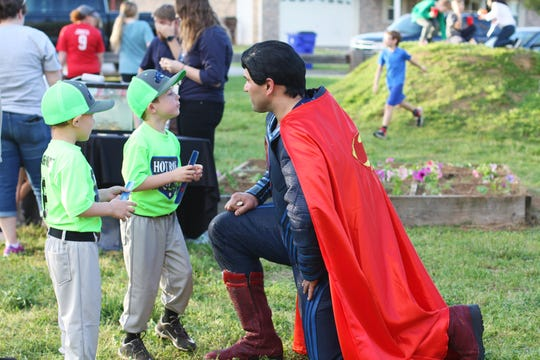 """Jase, left, and Michael Davenport chat with Superman. Former student Jarrod Davenport brought his sons to the Halls Outdoor Classroom spring event on April 16, 2019. """"Anything that Ms. Coley is involved in I'm there. It's hard to believe it's been 10 years,"""" said Davenport."""