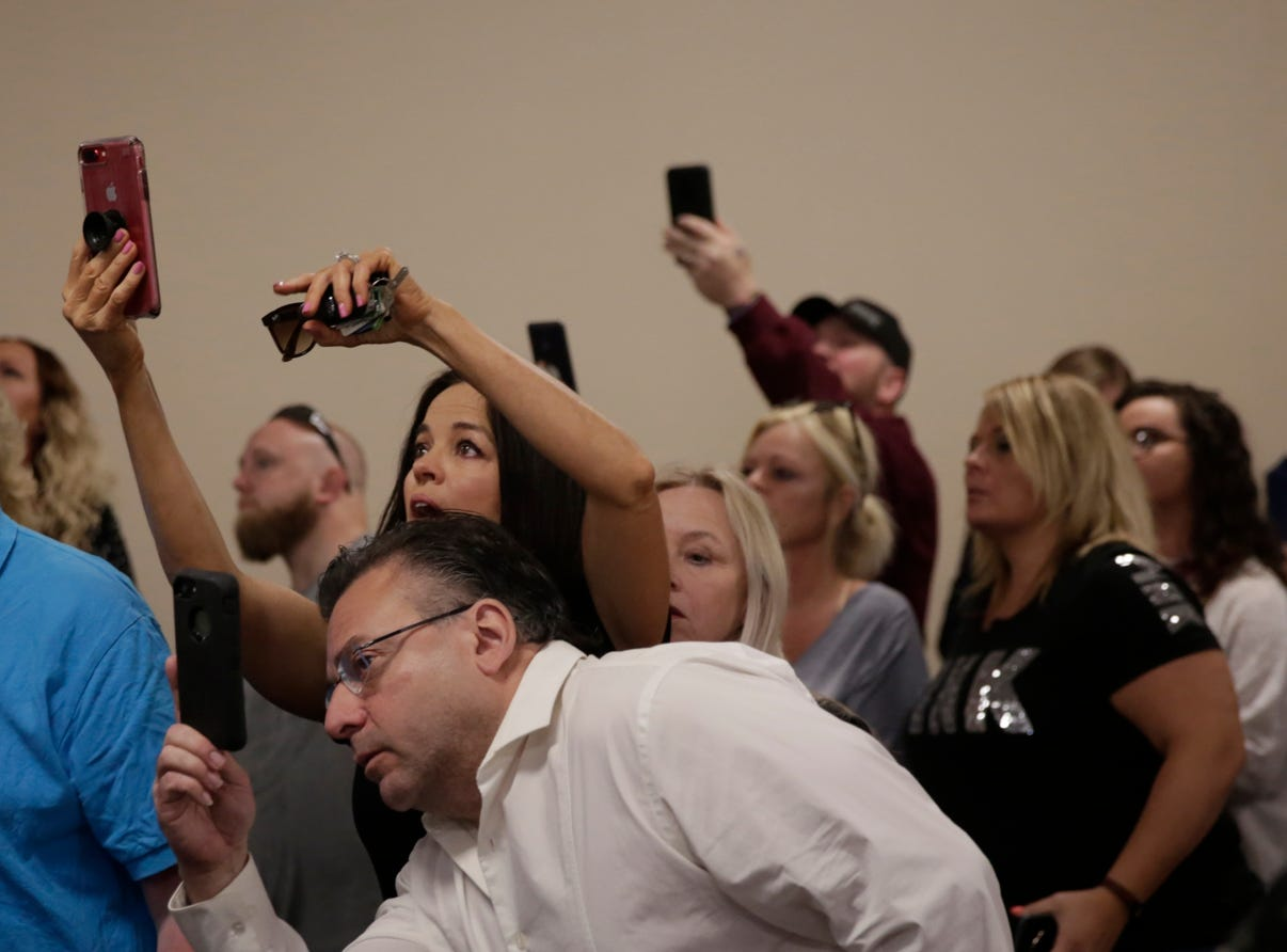 Community members strain to photograph a sketch of the suspect during a press conference on an update on the Delphi murders investigation, Monday, April 22, 2019 at the Canal Center in Delphi. Abby Williams and Libby German, both Delphi eighth-graders, were murdered while hiking a popular community trail near Delphi on Feb. 13, 2017.