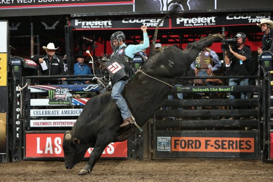 Fernando Henrique Novais attempts to ride Rickey West Bucking Bulls's Bam Bam Bigelo during the first round of the Columbus PBR 25th Anniversary Unleash the Beast. Photo by Andy Watson