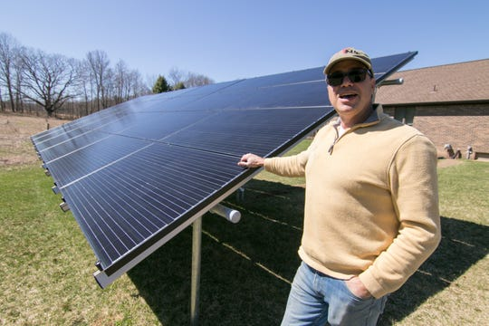 Brighton Township resident Jim Burgess talks about the power his solar panels produce as installers put up an array of panels at his son's house under construction next door Monday, April 15, 2019.