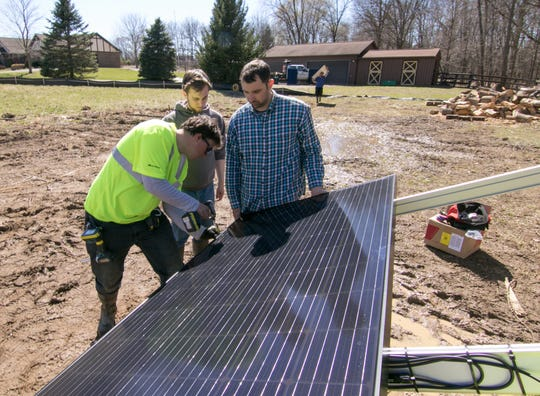 The Green Panel solar technician Corey Capraro tightens bolts on an array being installed in Brighton Township on Monday, April 15, 2019.