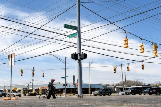 A cyclist approaches the intersection of South Martin Luther King Boulevard and West Holmes Road in on Monday, April 22, 2019, in Lansing. The location was the third most accident-prone intersection in Ingham County in 2017, according to Michigan State Police statistics.
