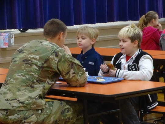 U.S. Army Spc. Shelby Dininger, a 2009 graduate of Lexington High School, Monday  catches up with his sons, Austin, 7, at left, and Blake, 10 during their lunch hour at Stingel Elementary. Their father just returned from a nine-month deployment in the Middle East.