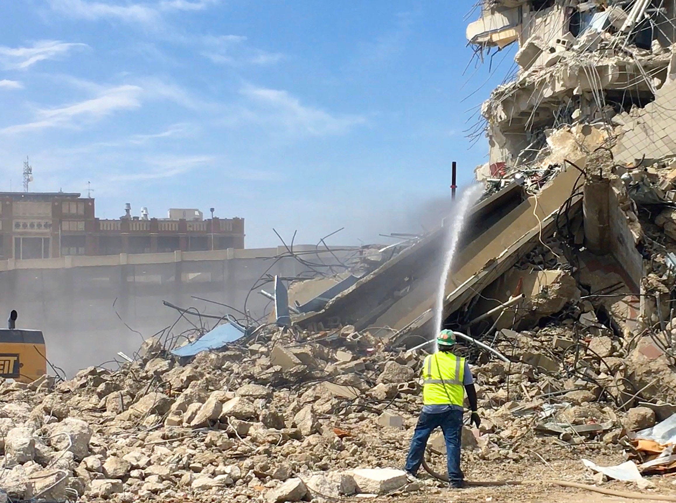Water is sprayed to reduce dust as work continues on the demolition.