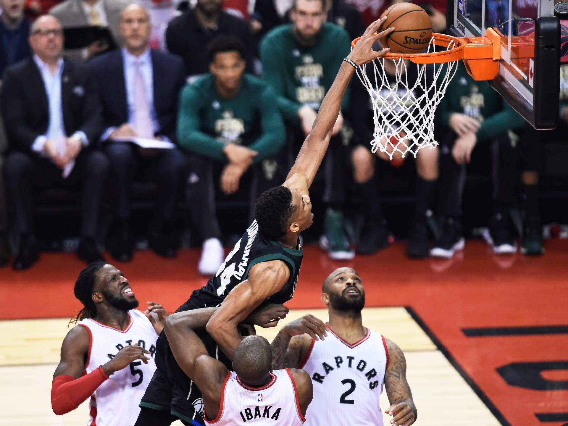 Milwaukee Bucks forward Giannis Antetokounmpo (34) dunks over Toronto Raptors forward DeMarre Carroll (5), forward Serge Ibaka (9) and forward PJ Tucker (2) during first-half NBA playoff basketball game action in Toronto on Saturday, April 15, 2017.