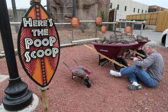 Don Evenson of Fast Signs attaches signs to wheelbarrows full of replica elephant dung at the new elephant exhibit at the zoo. They will provide a photo prop for visitors and information on the elephants' diet. Shield sign produced by Gietl Sign Co.