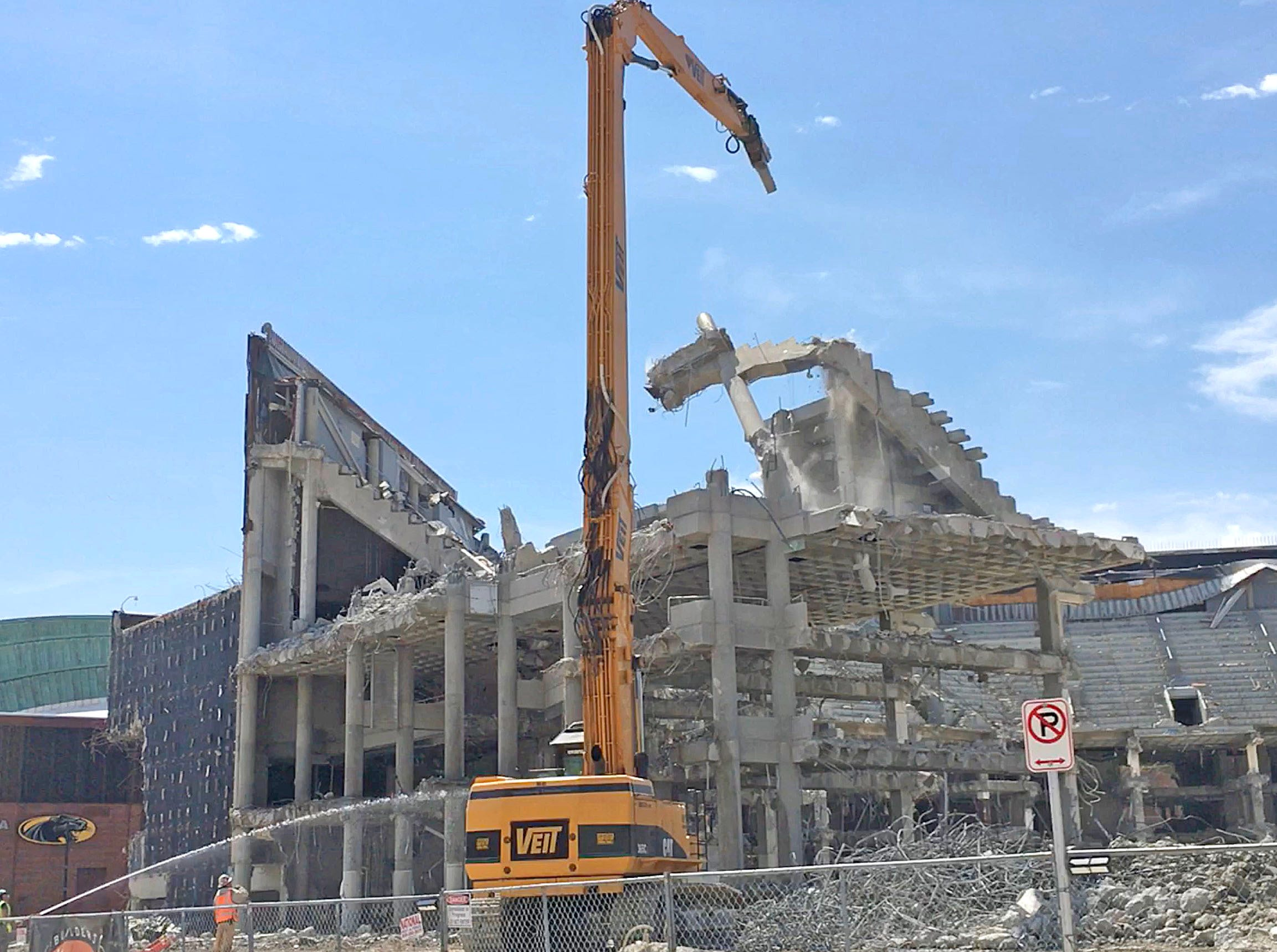 A beam from the upper bowl of the arena comes crashing down as work continues on the demolition.