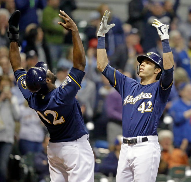 Brewers outfielder Christian Yelich (right) celebrates with Lorenzo Cain after hitting one of his three home runs in the game against the St. Louis Cardinals on Monday, April 15.