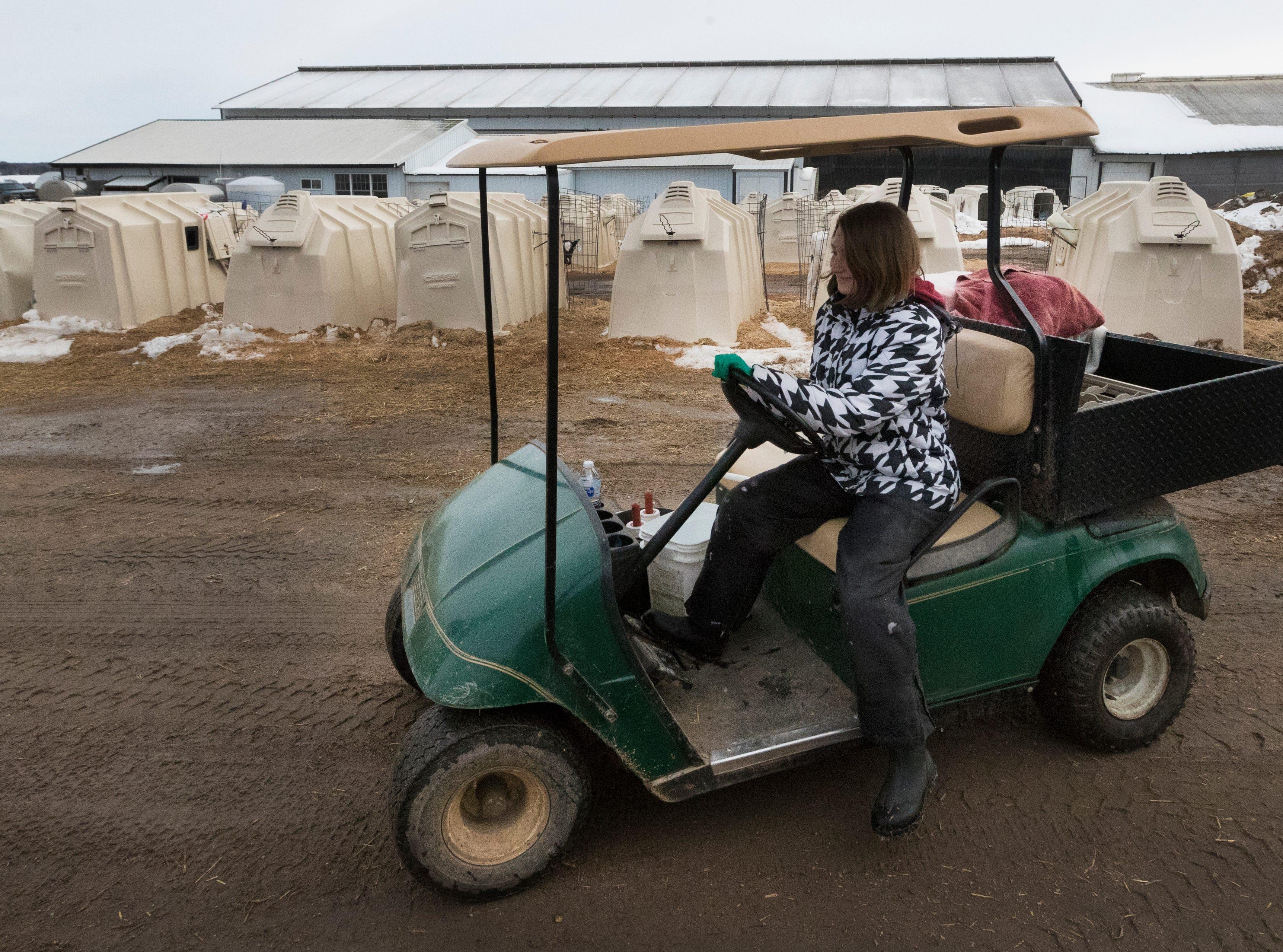 Maggie Breitenmoser, 14, feeds calves .
