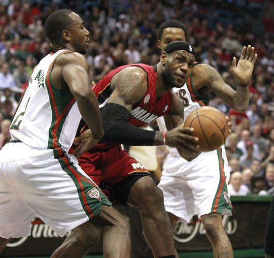 Milwaukee Bucks' Luc Richard Mbah a Moute and Brandon Jennings can't stop the Miami Heat's LeBron James in the first half during the 4th playoff game at the BMO Harris Bradley Center Sunday. the April 28, 2013.
