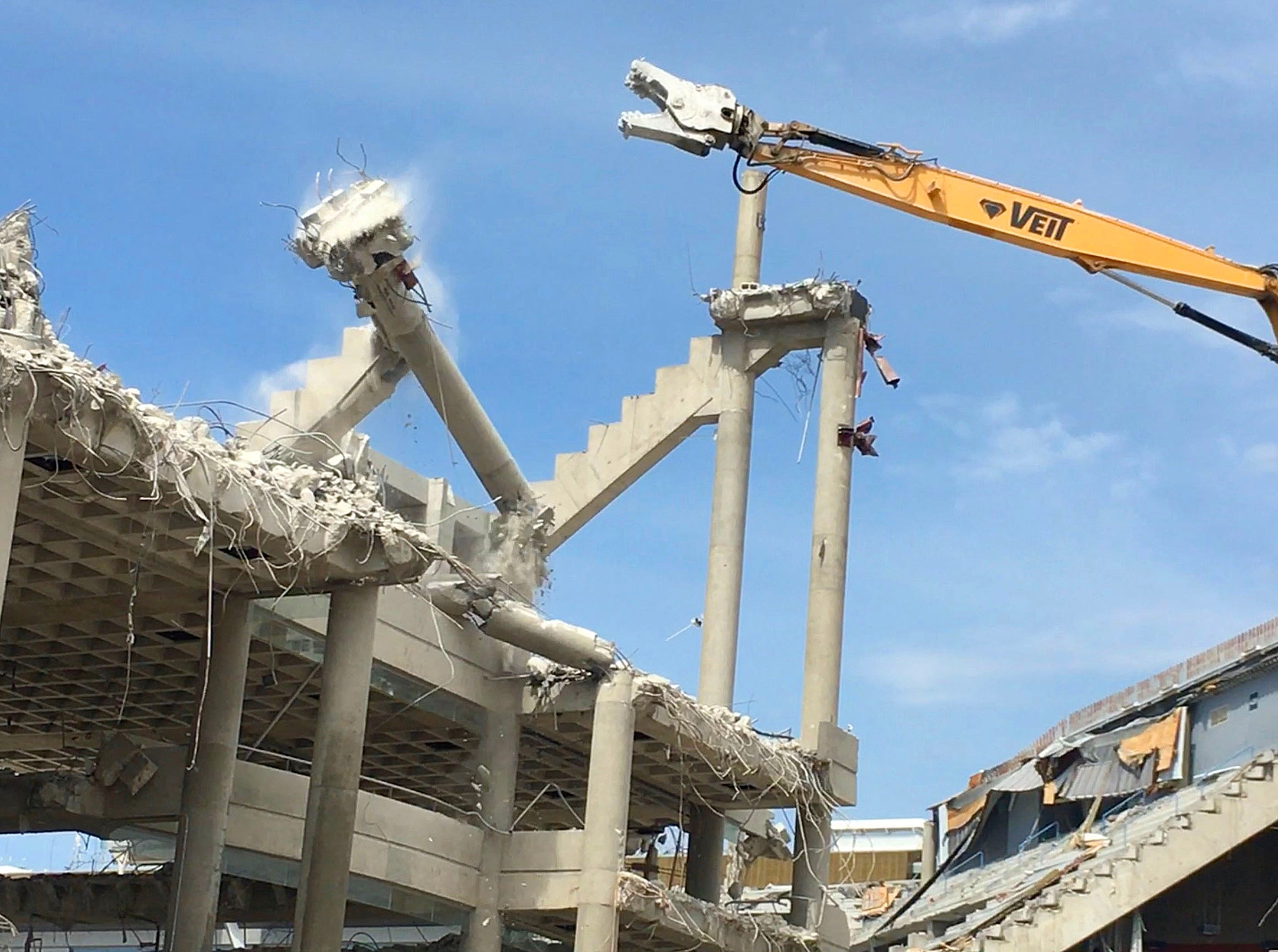 A beam from the upper bowl of the arena comes crashing down as work continues on the demolition of the BMO Harris Bradley Center in Milwaukee on Monday. The former home of the Milwaukee Bucks is being razed as the new Fiserv Forum was built just to the north.