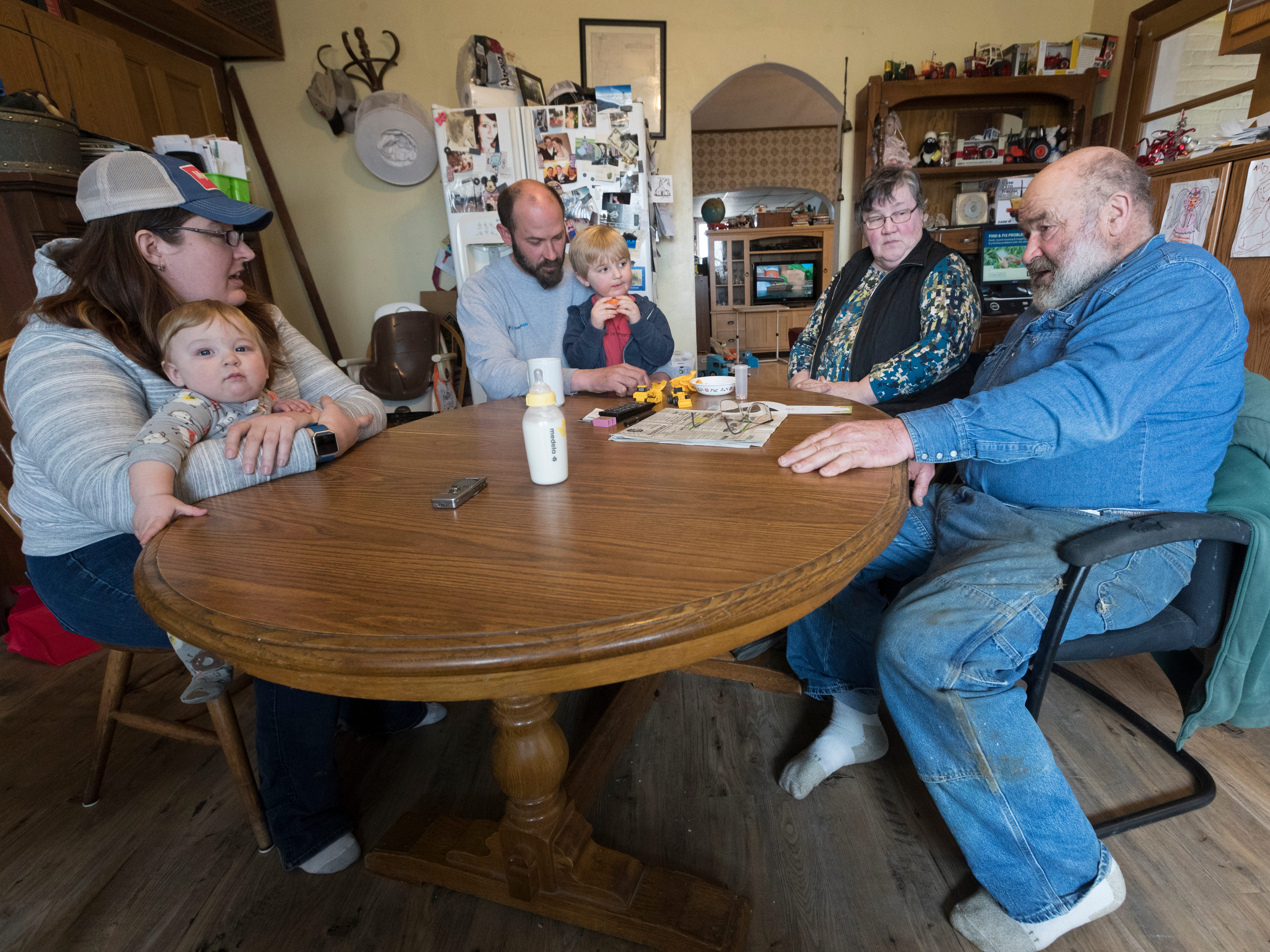 The Mess family, Carrie Mess, from left, with her 10-month-old son, Ben; husband, Patrick, with 3-year-old son Silas; and Cathy and Clem Mess, gather around their kitchen table on their farm in Watertown.