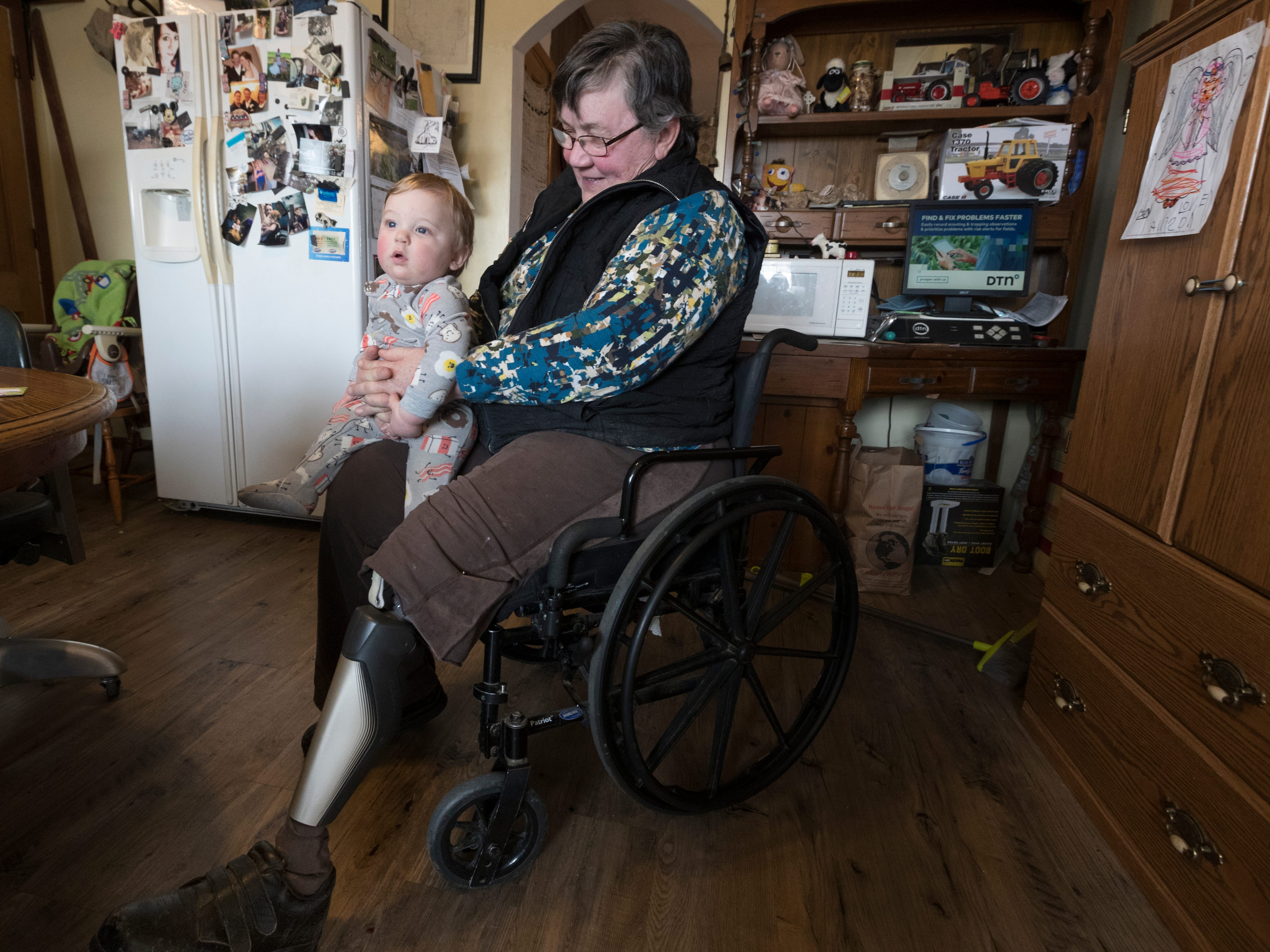 Cathy Mess holds her 10-month-old grandson, Ben. Mess used to help with many of the chores on the farm before she lost her left leg in a farm accident.
