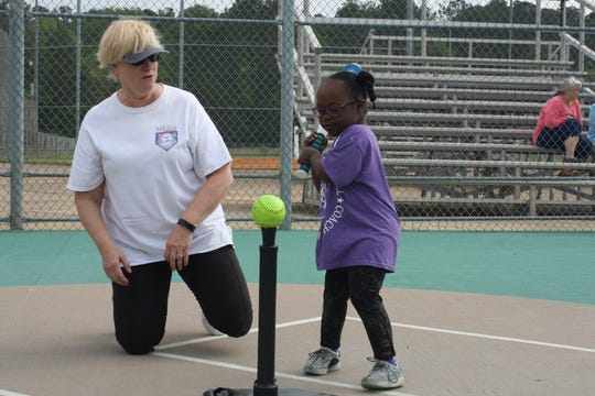 Miracle League volunteer Karen Agnello helps Abi Williams at the plate during a League game.