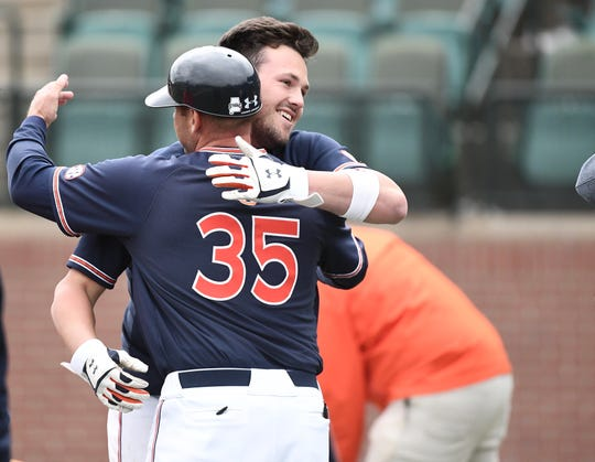 Auburn's Conor Davis hugs assistant Karl Nonemaker (35) after hitting a walk-off single to beat Ole Miss on April 20, 2019.