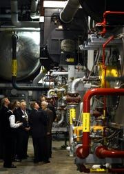 Council members, business leaders and others look over the inner workings of the District Energy System in late 2003.