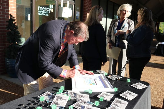 Ed Underwood signs Mercy's commemorative frame.