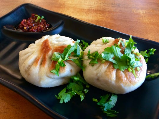 Pan-seared juicy pork bao with chili dipping sauce.