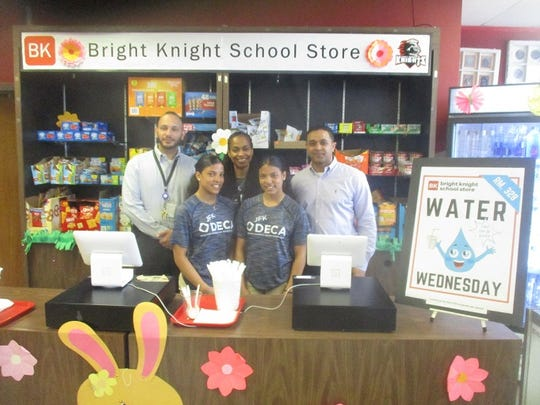 Twins Anyeli and Enyeli Galvez pose with Principal Jorge Osario of John F. Kennedy High School's BTMF Academy and DECA Advisors Martine Grant and Edwin Hernandez at JFK's Bright Knight School Store.