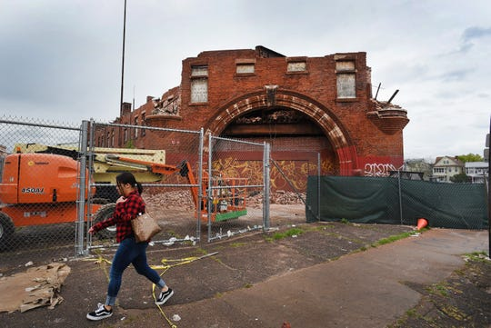 A woman walks past the remaining facade area of the Paterson Armory during its demolition in Paterson on 04/22/19. The armory was once a vibrant community hub that was vacant for decades before much of it was destroyed in a 2015 fire.