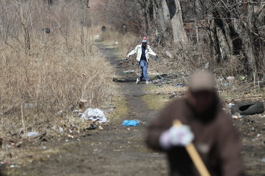 A man holding two beer cans has trouble walking as he stumbles through an area with railroad tracks near the intersection of Wall and 6th St. in Passaic.  The area is known as a place where people come to do drugs and prostitution.  The Passaic DPW (foreground) was there Thursday, April, 4, 2019 to clean the area.