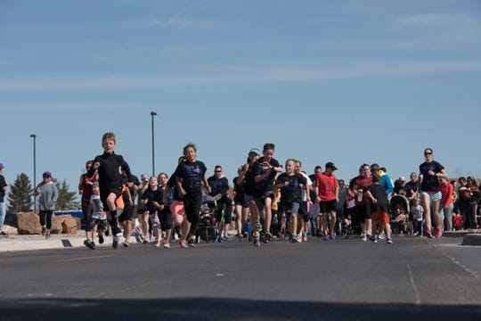 Participates take off from the starting line of an Autism Awareness fun run on Holloman Air Force Base, April 6, 2019. Over 750 people participated in the fun run and children's carnival.
