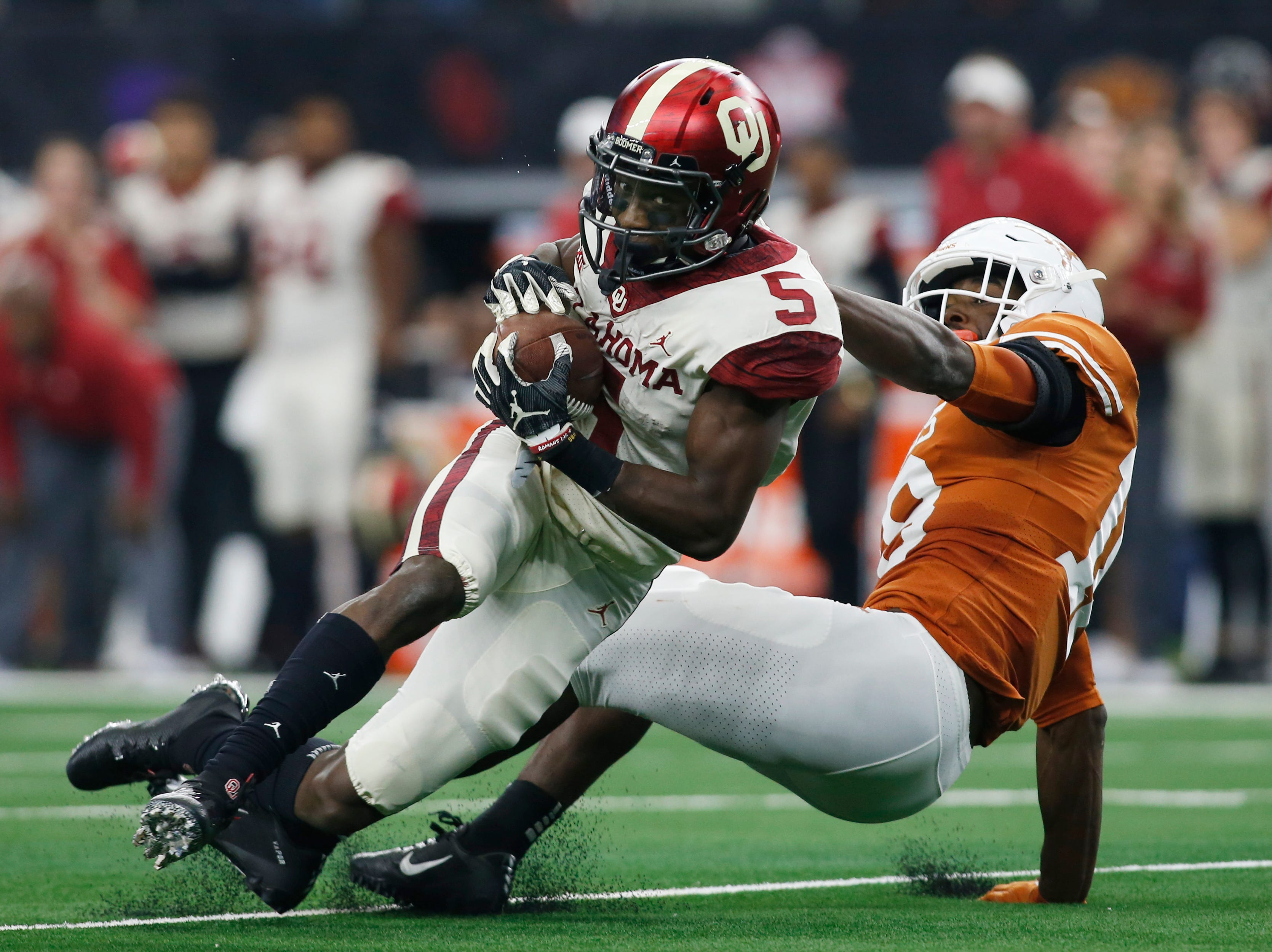 Oklahoma receiver Marquise Brown is brought down by Texas defensive back Davante Davis during the Big 12 championship game.