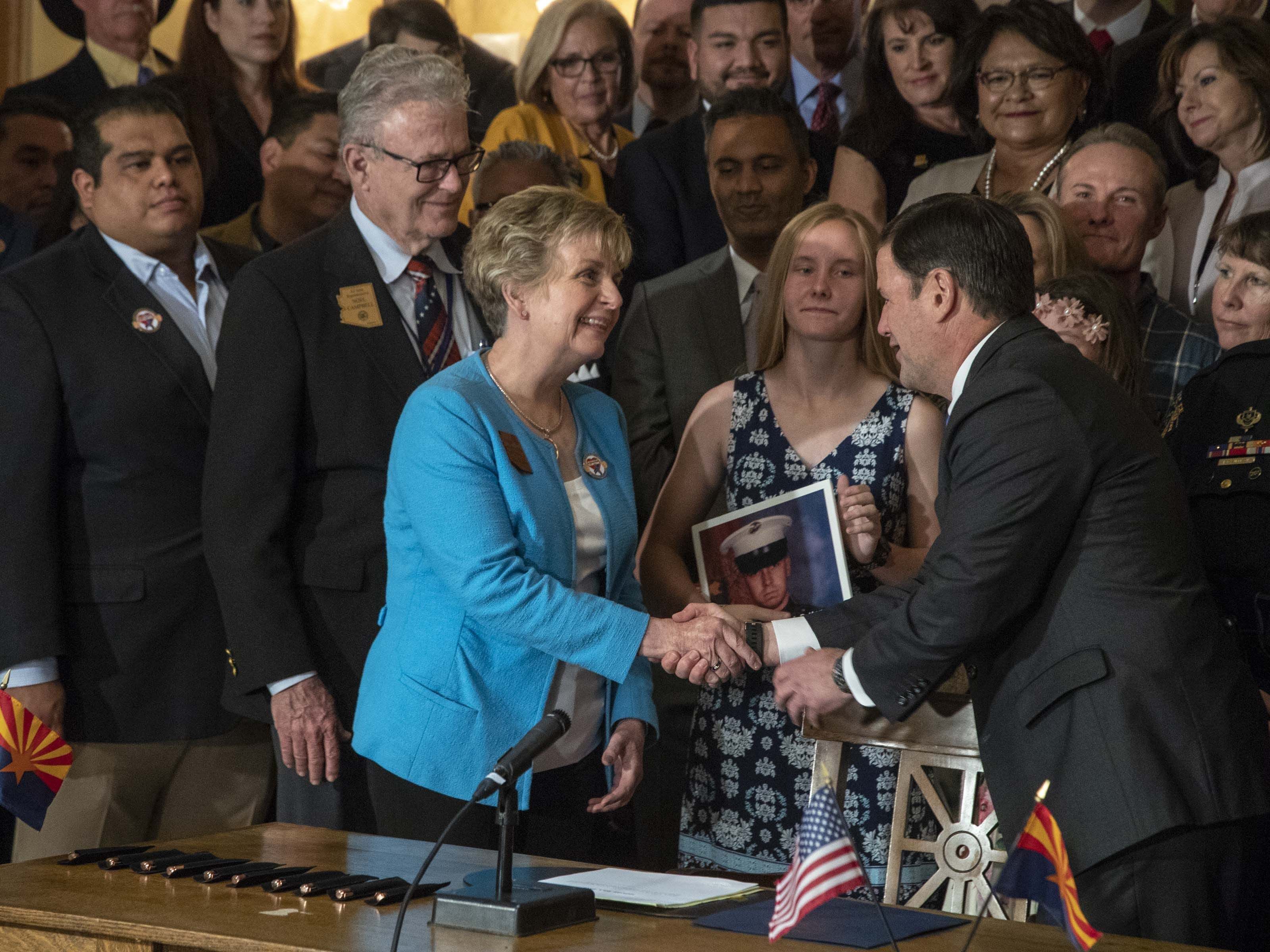 Gov. Doug Ducey shakes Sen. Kate Brophy McGee's hand during the signing of HB 2318 in the Rotunda of the Arizona Capitol Museum on April 22, 2019. The bill prohibits texting while driving in Arizona.