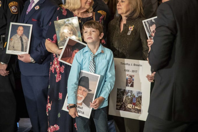 Aiden Hall, 8, holds a poster of his grandfather, Tom Hall, while Gov. Doug Ducey signs a bill that prohibits texting while driving on April 22, 2019. Hall died in Prescott Valley in 2016 when a distracted driver hit him. Aiden and his father, Jonathan Hall, of Peoria, have been advocating for a state law since then.