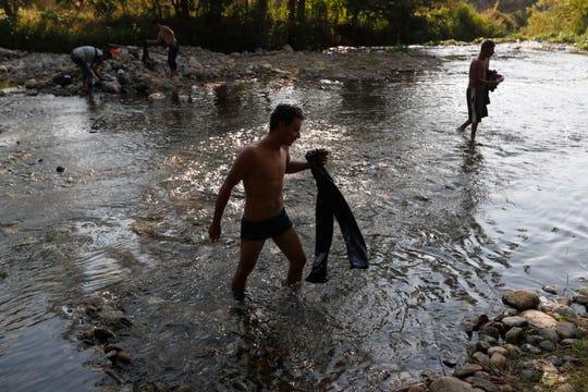 Varios hombres se bañan en un río en Chiapas.