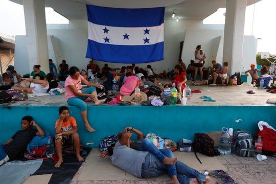 Una bandera de Honduras es desplegada en un refugio en el que permanecen varios migrantes.