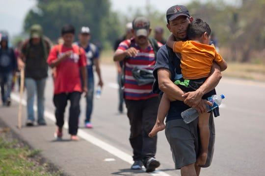 Un migrante centroamericano recorre un tramo por Chiapas con su hijo pequeño en brazos.