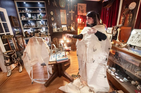 Lauren Rae, owner and curator, tries on a mummy suit for sale that was used in sanitariums to restrain someone with mental illness. The first floor of new The Dark Parlour Haus of Obscurities, opening June 28, is a retail space.