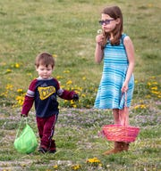 Kenadee Virgilio, 9, blows on a dandelion while her brother Maddox Cleland, 2, hunts for eggs during Living Stones' Easter hunt.