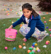 Kendall Sanchez, 6, gathers eggs on the lawn at Crosswinds Church.