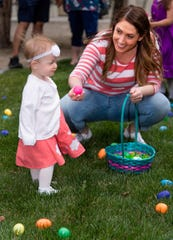 Hailey Rothgeb, 18 months, of Fernley, gathers eggs with her mother, Kelly Rothgeb.